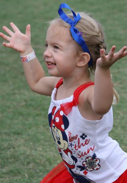 Little girl with blue ribbon playing at the 4th of July celebration.